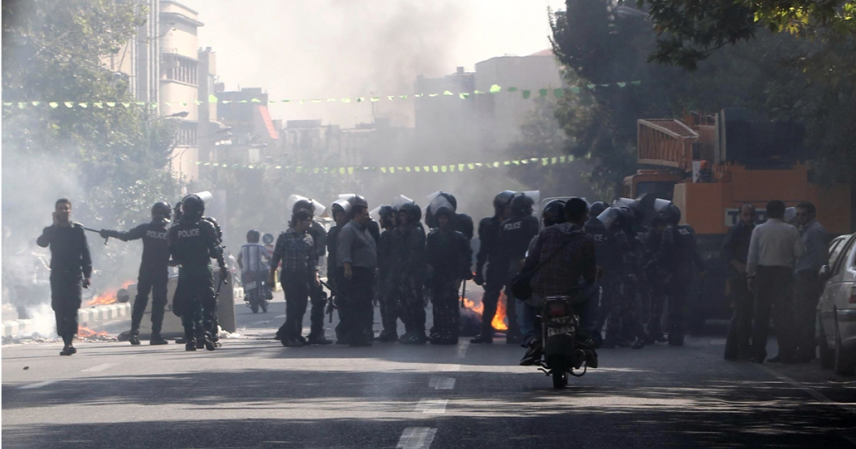 Iranian riot police stand next to a garbage container which is set on fire by protesters in central Tehran, near the main bazaar, on October 3, 2012, in the first sign of public unrest over Iran's plunging currency. The rial, lost more than half of its value since last week as the plunge has greatly increased inflation in Iran, which is widely seen as far higher than the official 23.5 percent given by the central bank.</p>