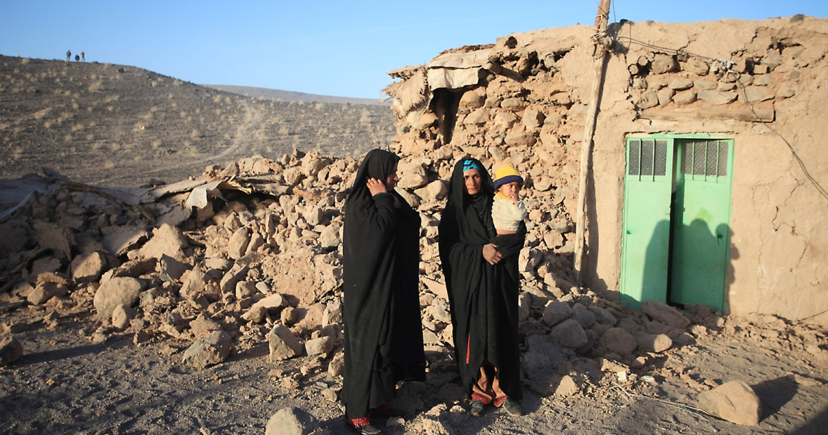 Iranian women and a child stand outside their damaged house in the village of Chah Ghanbar after an earthquake struck southeastern Iran in December 2010.</p>