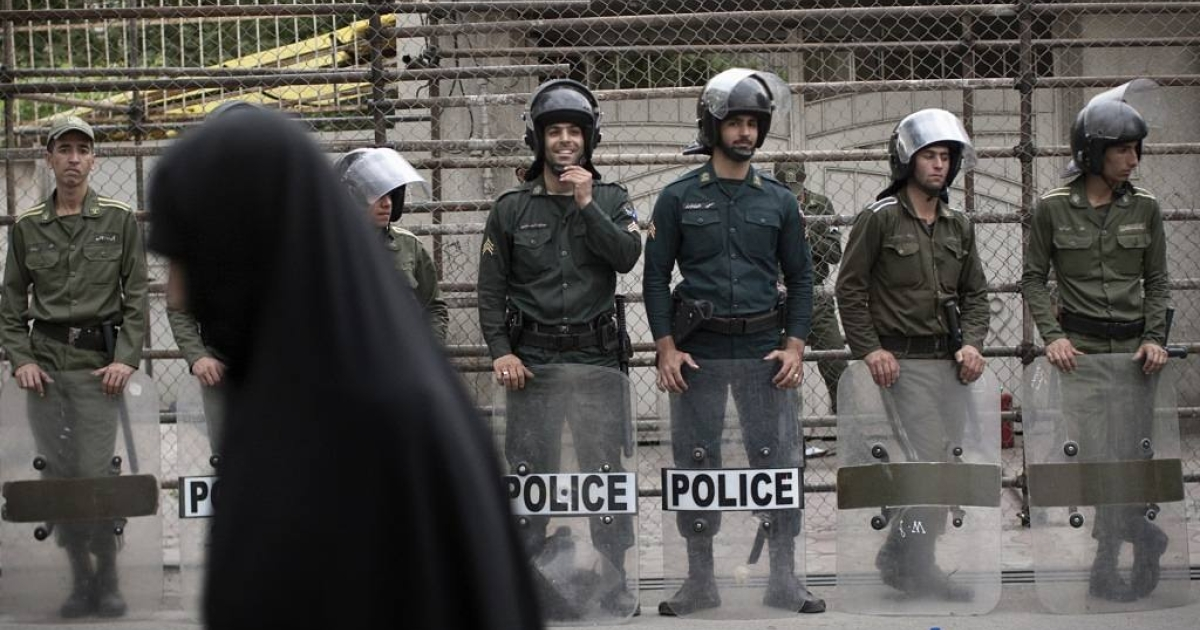 An Iranian hard line student walks past riot police during a protest in Tehran on April 30, 2011.</p>