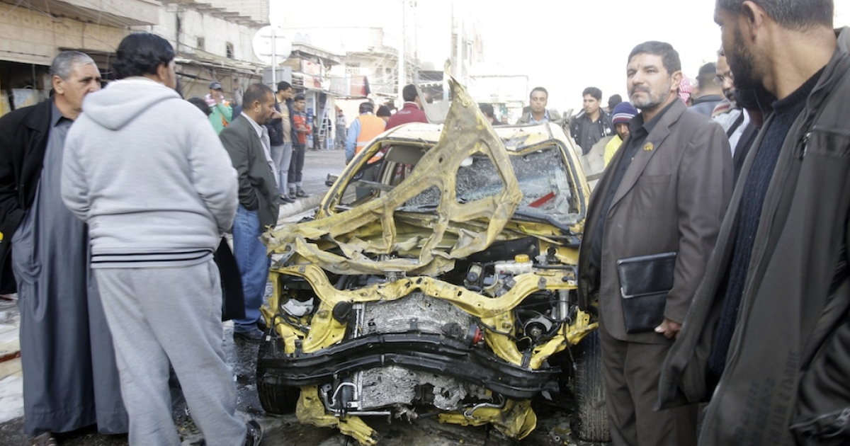 Iraiqs inspect the scene in the north Baghdad neighbourhood of Kadhimiyah where twin car bombs exploded on January 5.</p>