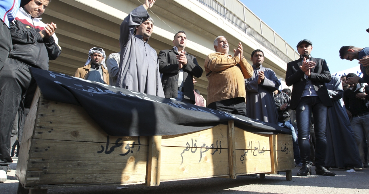 Iraqis protest in front of a coffin representing the