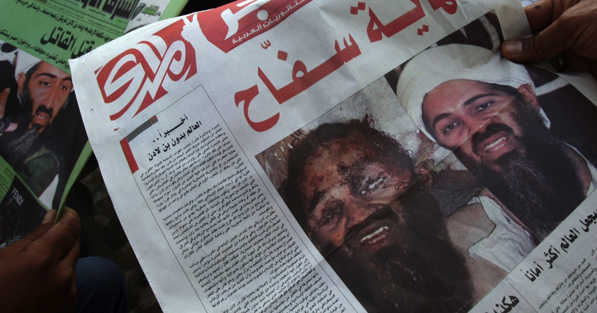 Iraqi men read newspapers displaying front page pictures and headlines that read in Arabic
