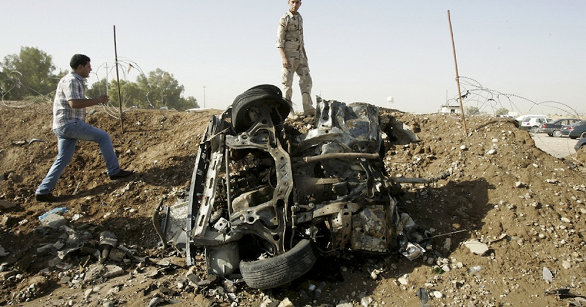 Iraqis inspect the site of a blast in a car park at the rear gate of the the state-owned North Oil Company, about 9 miles from the northern city of Kirkuk, on September 9, 2012. A series of at least 10 attacks across Iraq, including a bombing at a state-owned oil company, killed more than 30 people and wounded over 80 others, security and medical officials said.</p>