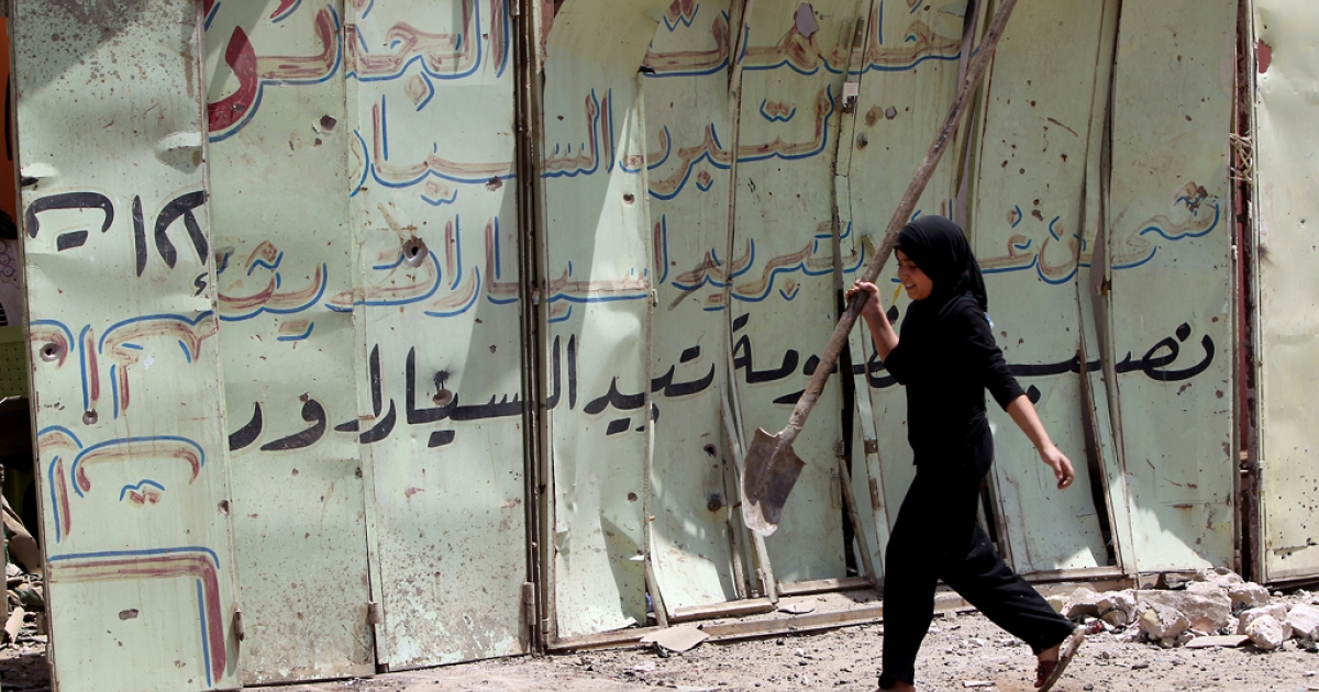 An Iraqi girl walks past the site of a roadside bomb in Baghdad's Karrada district on June 13, 2012 as a wave of bombings and shootings rocked Iraq during a major Shiite religious commemoration, killing scores of people and wounding dozens more.</p>