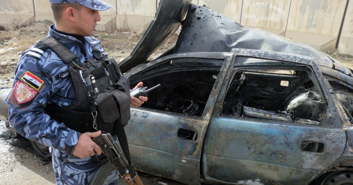 An Iraqi soldier stands close to a destroyed vehicle following a road side bomb on February 13, 2012. A car bomb near a police academy killed 20 police recruits in Baghdad on February 19, 2012.</p>