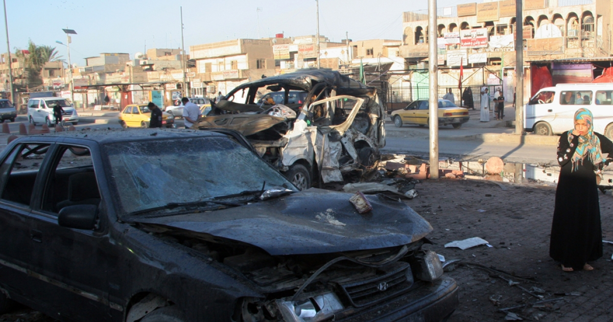 An Iraqi woman looks at the wreckage of a site of a car bomb, in Baghdad's Sadr city. Another car bomb killed at least 25 army recruits in the town of Taji on November 6, 2012.</p>