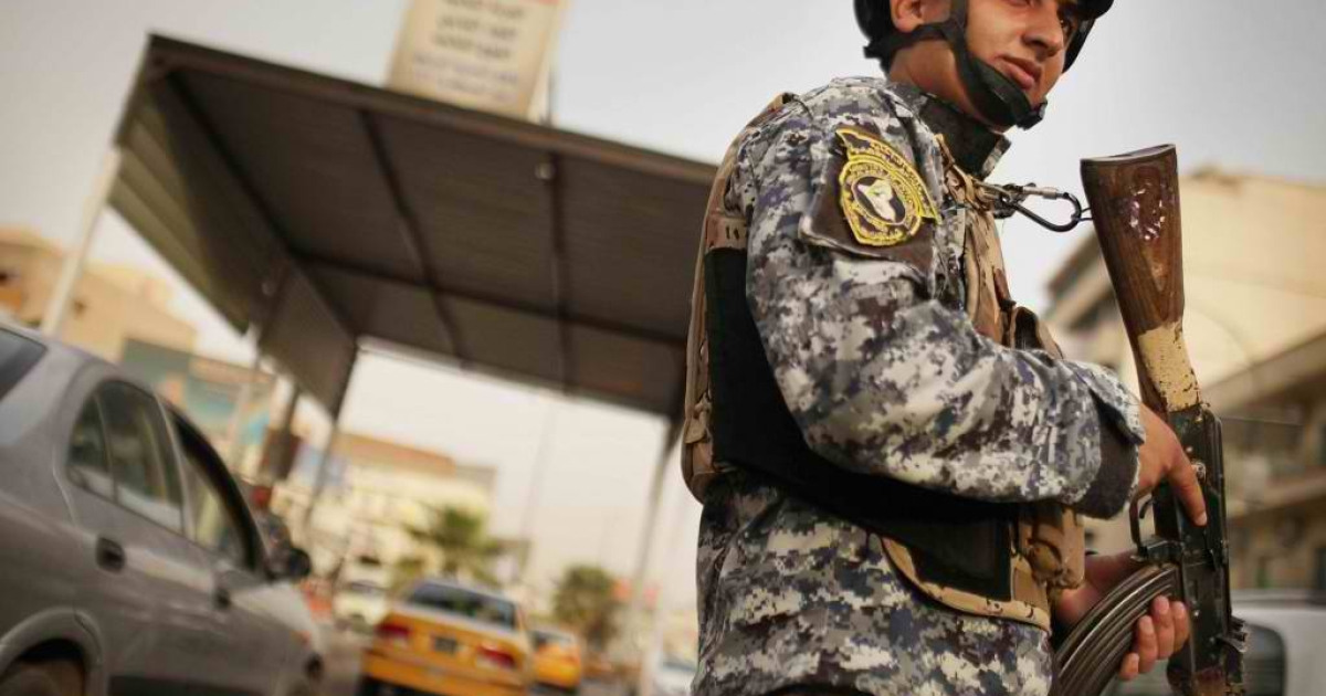 An Iraqi police officer watches cars at a checkpoint on July 20, 2011 in Baghdad. A new report says security in Iraq is deteriorating.</p>
