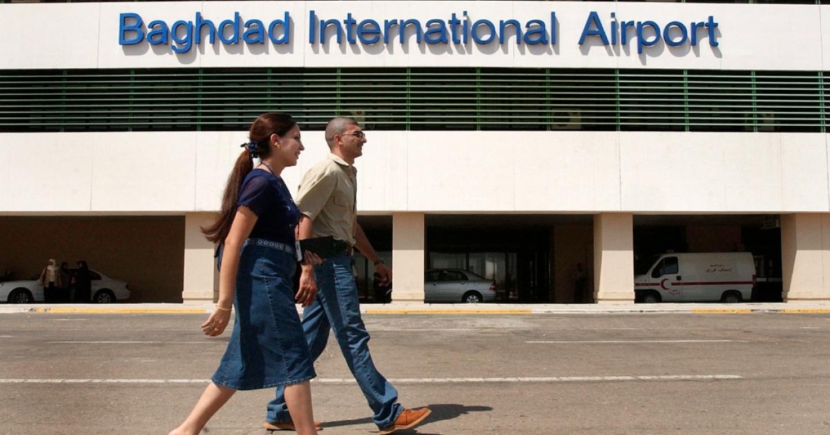 Iraqis walk near Baghdad International Airport in 2004.</p>