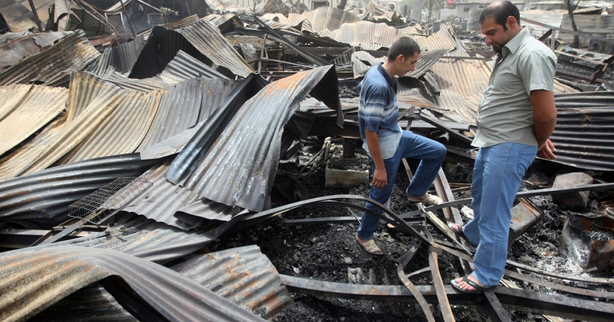 Iraqis look at the damage at the scene of a rocket attack on a residential compound in central Baghdad, on July 5, 2011.</p>