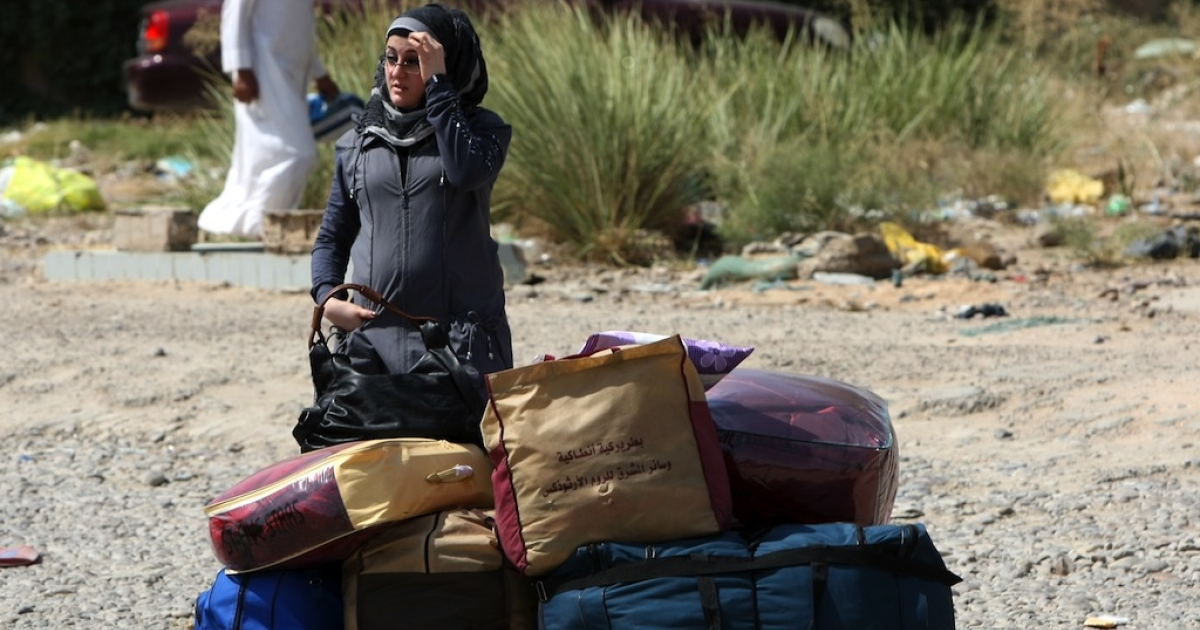 An Iraqi refugee, who had fled to Syria following the 2003 US-led invasion of Iraq, waits next to her belongings upon her arrival in Baghdad on July 3, 2011.</p>