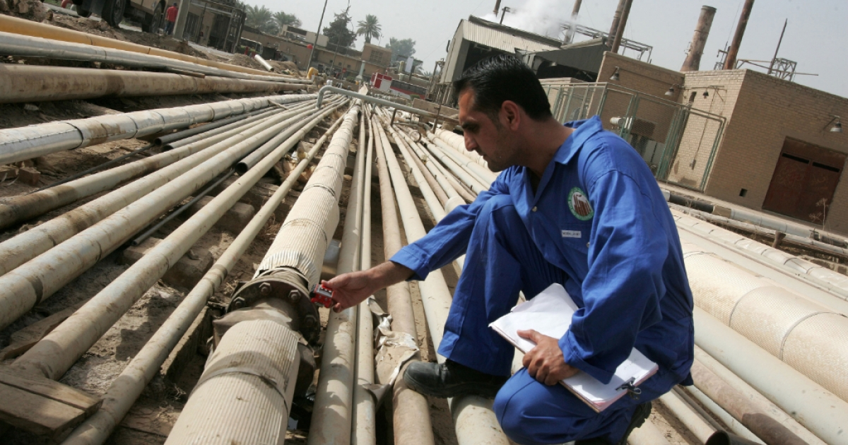An Iraqi worker examines gas emissions from an oil pipe at a refinery in Baghdad.</p>