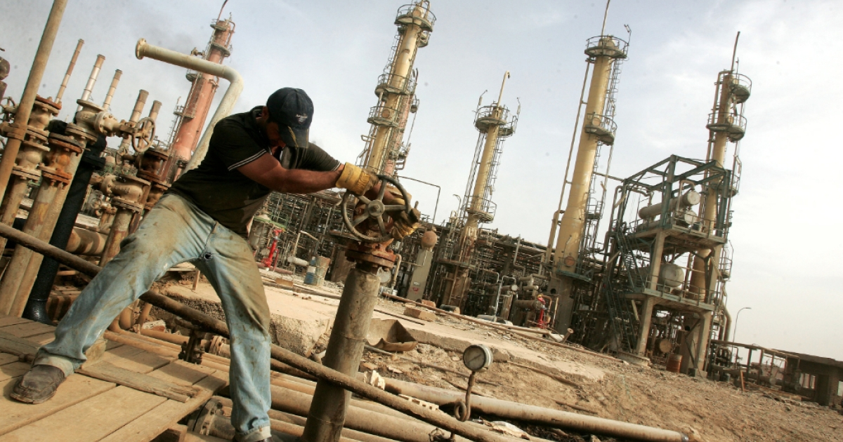 An Iraqi worker works a control valve at the Daura oil refinery in Baghdad, Iraq, 2009.</p>