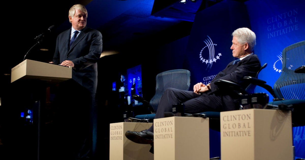 Denis O'Brien, chairman of Digicel, converses with former U.S. President Bill Clinton before the panel session