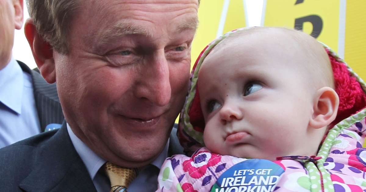 The center-right Fine Gael party, led by Enda Kenny, will form a new Irish government after winning the election. Here Kenny smiles as he holds 6-month-old May Hennelly during the campaign.</p>