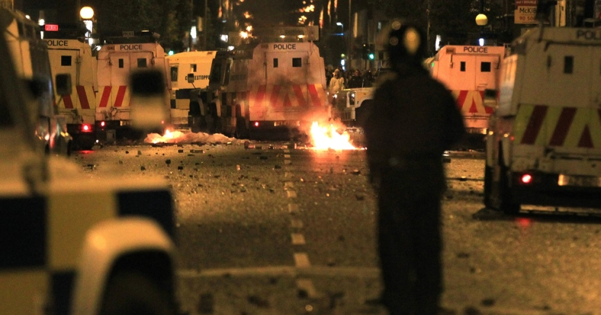 A policeman stands burning amid debris and police vehicles in east Belfast, Northern Ireland on June 21, 2011.</p>