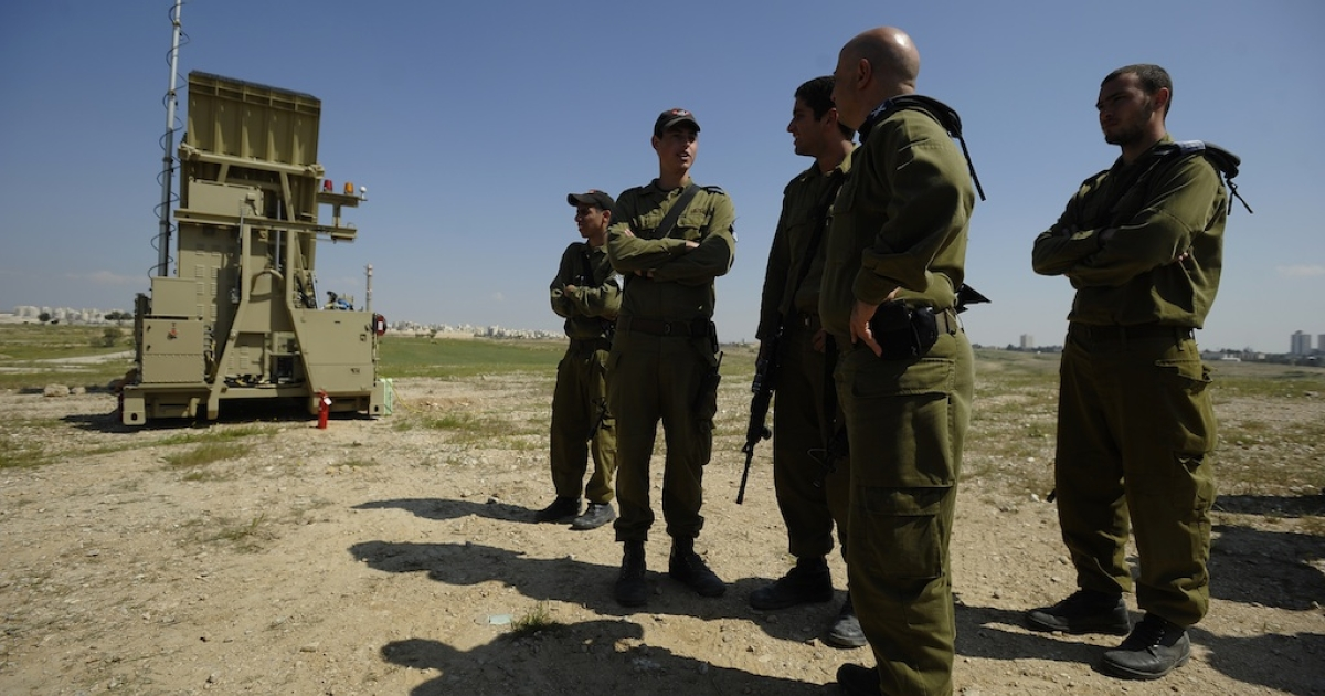 Israeli soldiers stand next to a launcher, part of the first Iron Dome missile defense system deployed in Israel, near the southern city of Beersheva on March 27, 2011.</p>