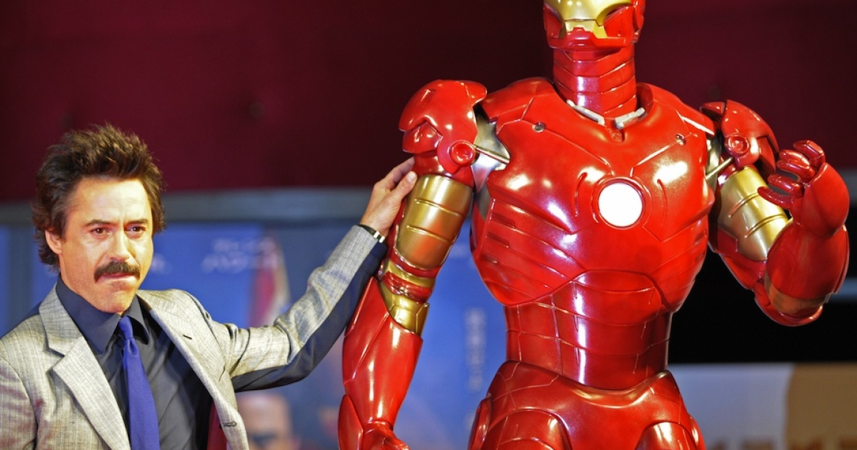 Robert Downey Jr. poses by a life-size Iron Man model during a press conference on his latest movie Iron Man, in Tokyo, on Sept. 3, 2008.</p>