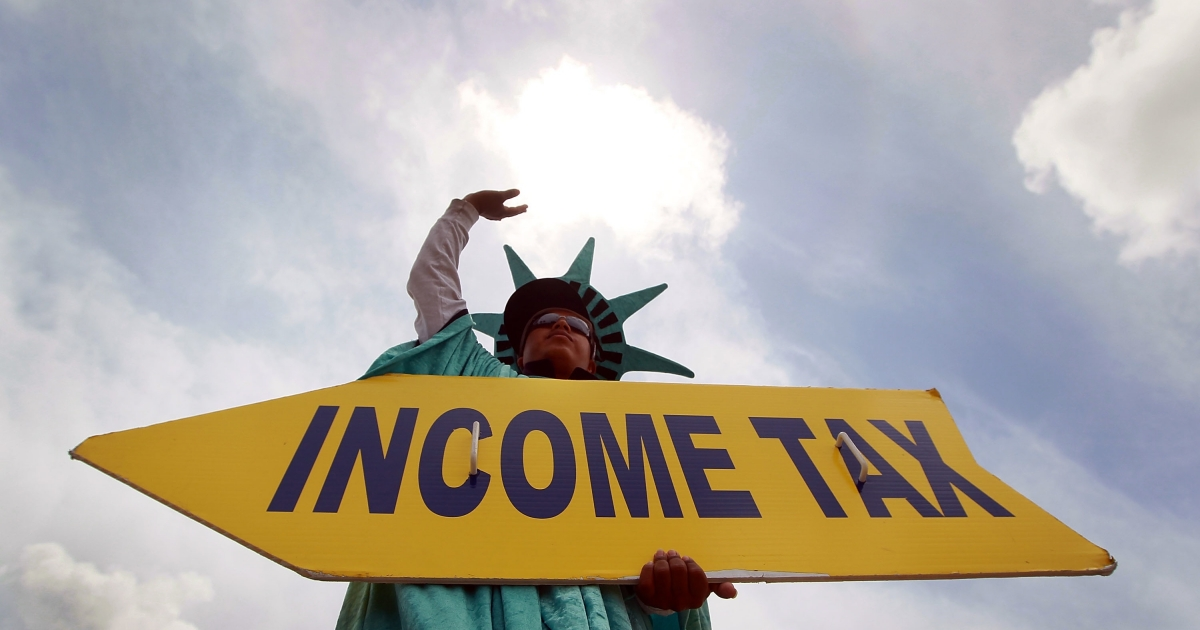 Felipe Castro holds a sign advertising a tax preparation office in Miami Beach, Fla., on April 14, 2010.</p>