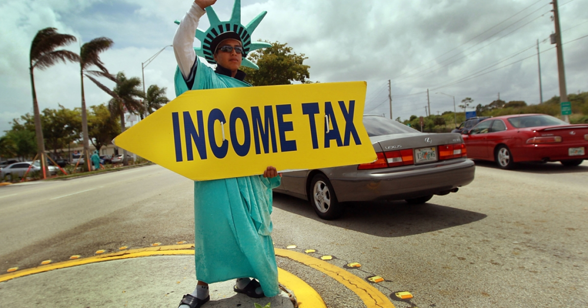 Felipe Castro holds a sign advertising a tax preparation office for people that still need help completing their taxes before the Internal Revenue Service deadline in Miami, Florida. The IRS is offering breaks to taxpayers struggling to file due to unemployment or reduced income.</p>