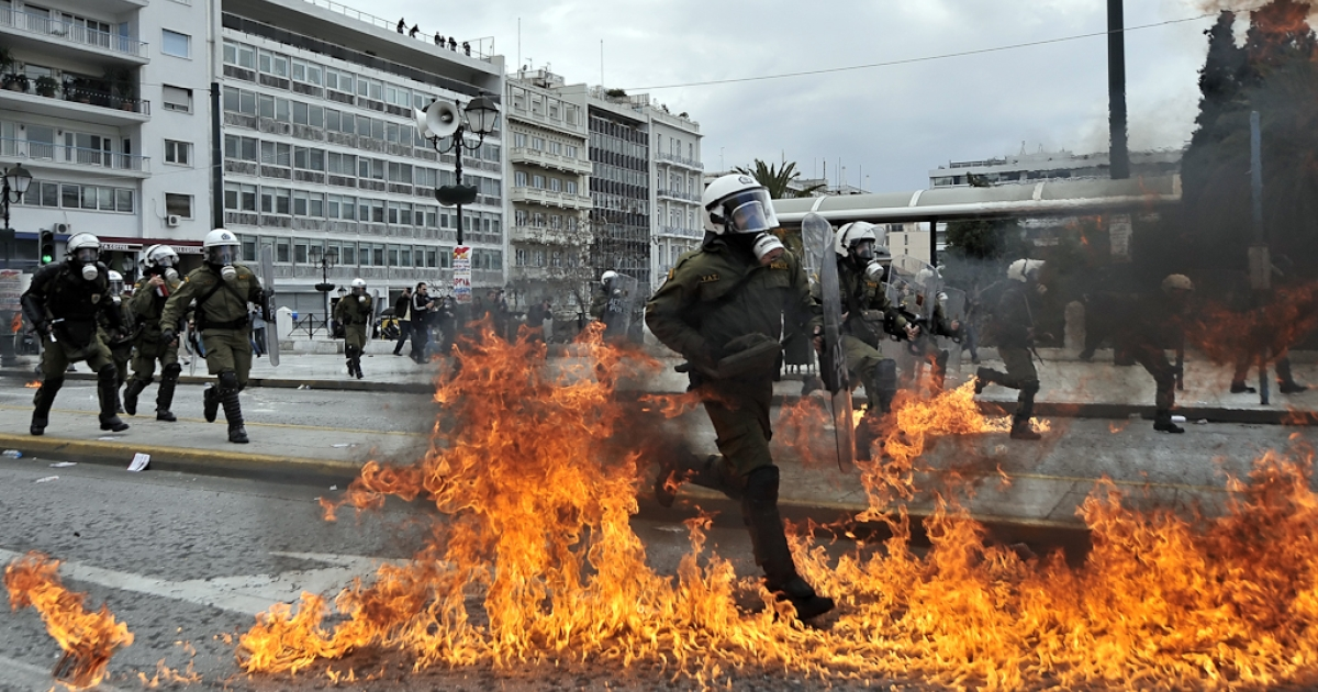 A police member runs through flames during clashes with demonstrators in central Athens on February 23, 2011.</p>