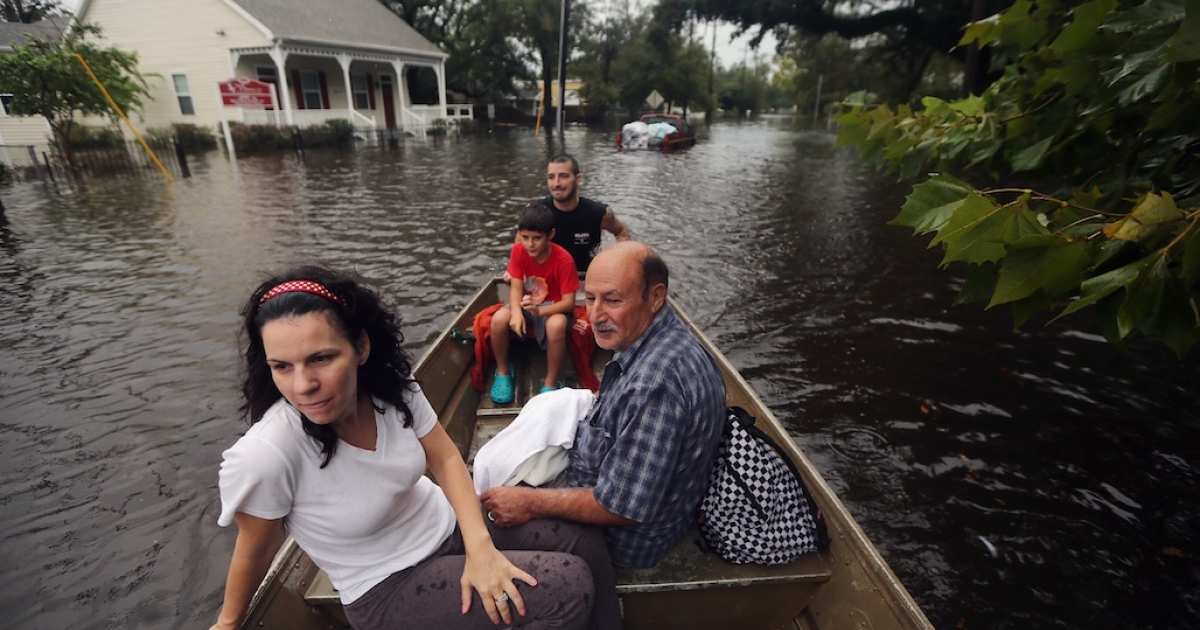 Joshua Barbot (back) rescues family members (L to R) Christie, Ethan and Larry Trumbaturi from their flooded home in his boat on August 30, 2012 in Slidell, Louisiana. The Isaac weather system has now been downgraded from a hurricane to a tropical storm but is still producing heavy rains and flooding as it moves north.</p>