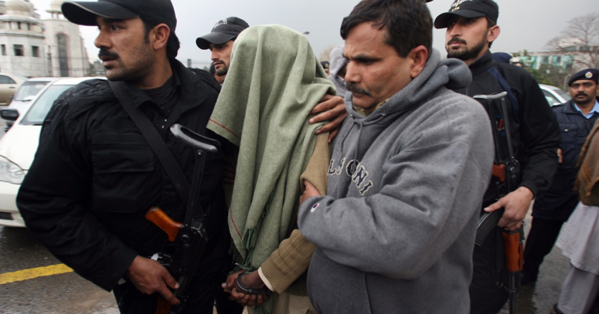 Pakistani policemen escort a man, seen draped in a shawl, after an appearance at the Supreme Court in Islamabad on February 13, 2012. Seven men allegedly held by Pakistan's feared intelligence services on February  appeared in court, an unprecedented development following orders from the country's highest court.   AFP PHOTO/Farooq NAEEM</p>