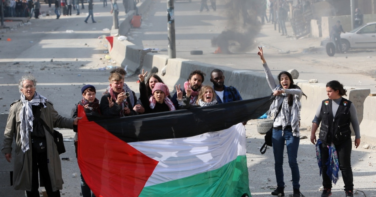 International peace activists hold the Palestinian flag during the commemoration of Land Day in Qalandia, which lies between Jerusalem and the West Bank city of Ramallah on March 30, 2012.</p>