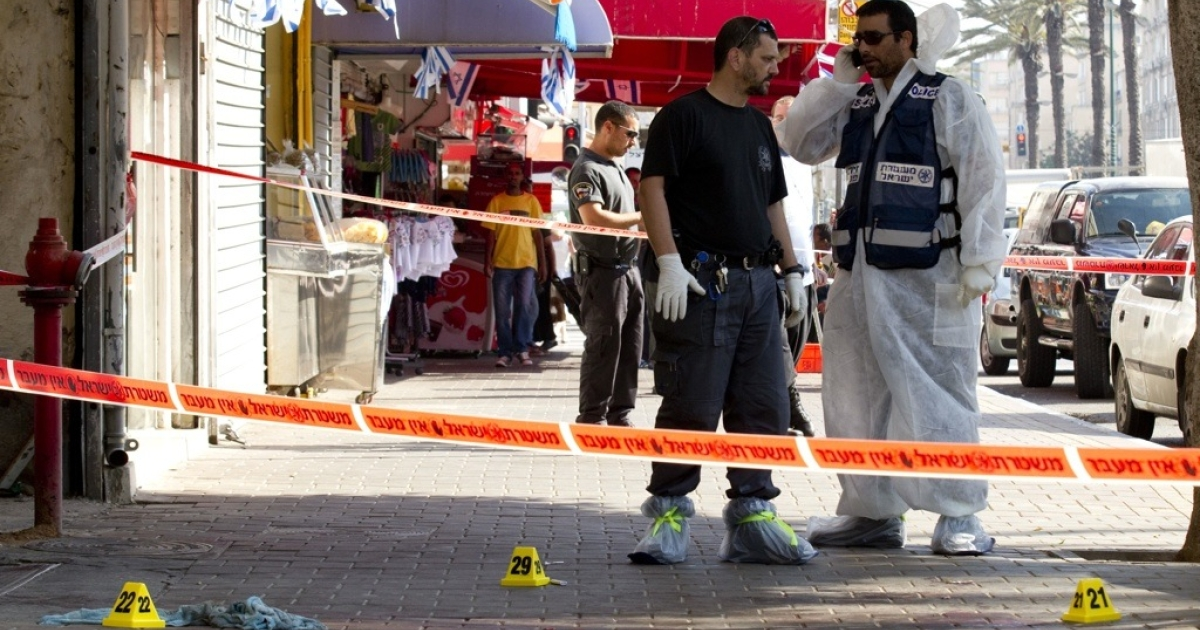 Israeli policemen inspect a crime scene, where a man was stabbed by knife, in the Mediterranean city of Netanya north of Tel Aviv on May 11, 2012.</p>
