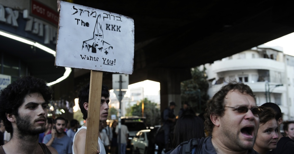 Left-wing Israeli protesters raise a sign picturing a member of the Klu Klux Klan (KKK) in opposition to a right-wing demonstration against African migrants in the city of Tel Aviv on May 30, 2012.</p>