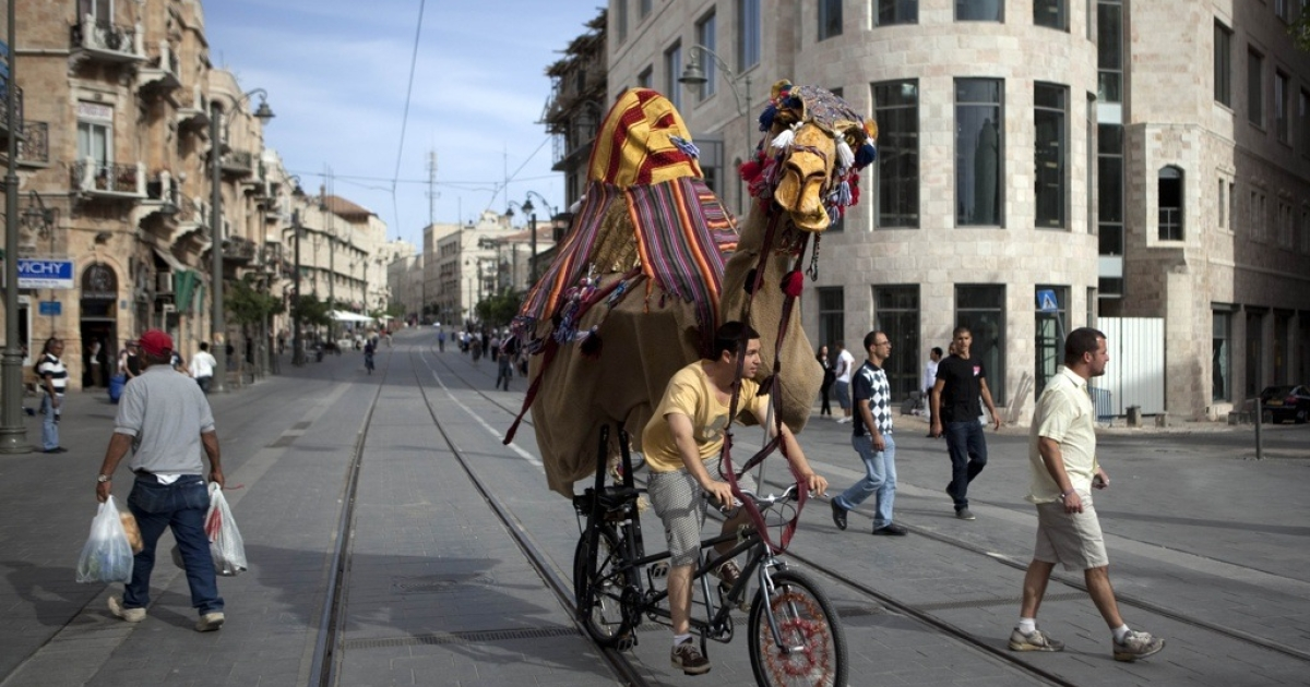 A man rides a bicycle with a camel effigy on Jerusalem's Jaffa street on May 26, 2011 during a street entertainment activity.</p>