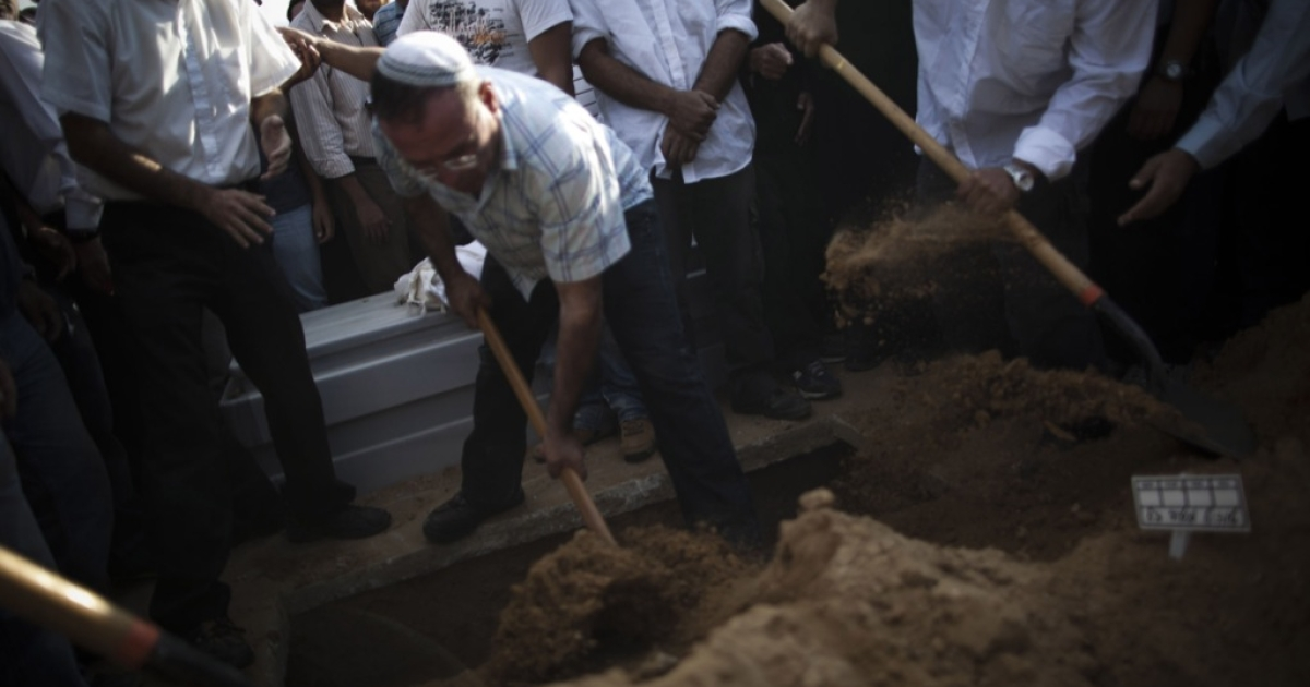 Men shovel dirt onto the grave as friends and relatives of the Ami family mourn their loss at the funeral of Moshe Ami, 56, a father and resident of Ashkelon, at the Ashkelon cemetery on October 30, 2011 in Ashkelon, Israel.</p>