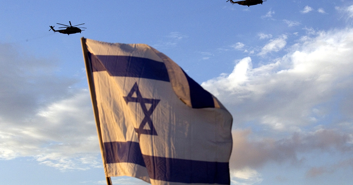 Israelis wave flags as helicopters transporting Israeli soldier Gilad Shalit and his family prepare to land at their home town of Mitzpe Hila following a landmark deal with Hamas which freed Gilad after five years of captivity, on October 18, 2011.</p>