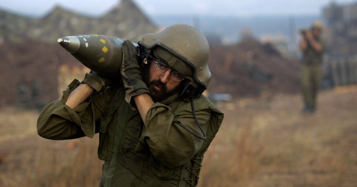 An Israeli soldier carries shells on the border with Lebanon in 2006.</p>