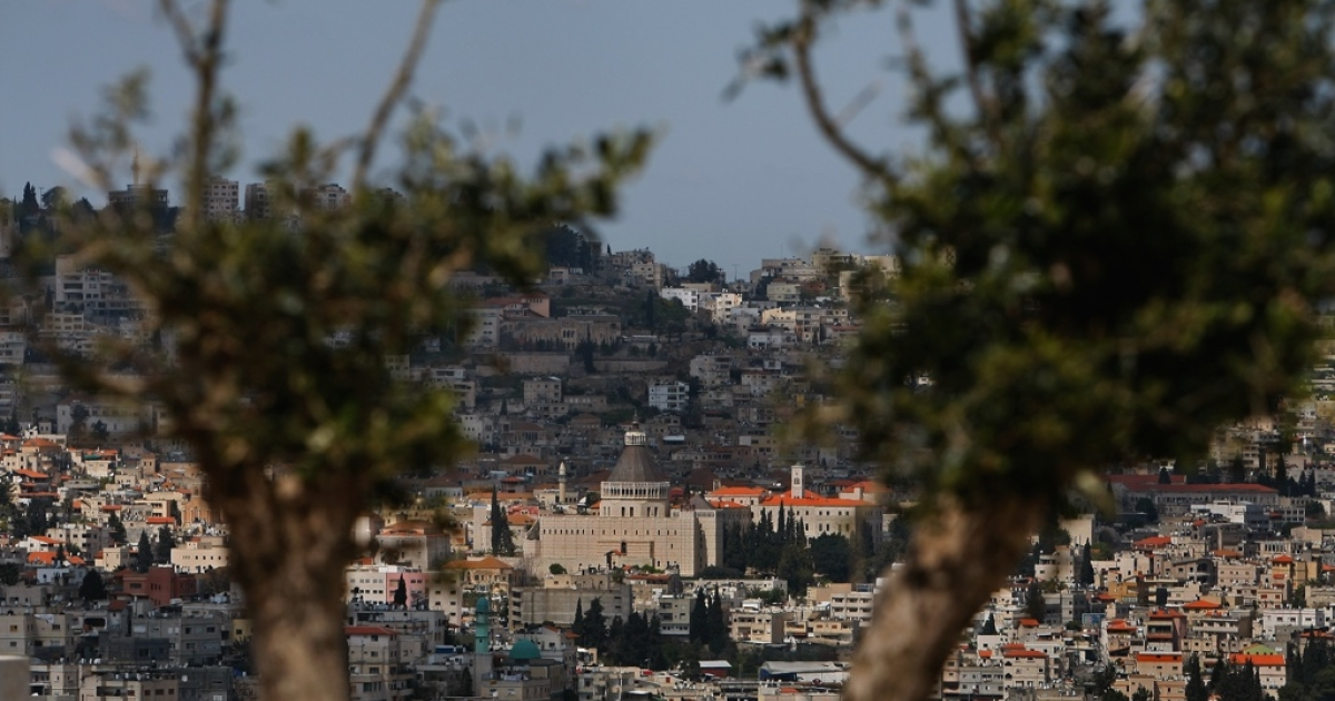 The Galilee town of Nazareth in northern Israel, seen between the branches of an olive tree.</p>
