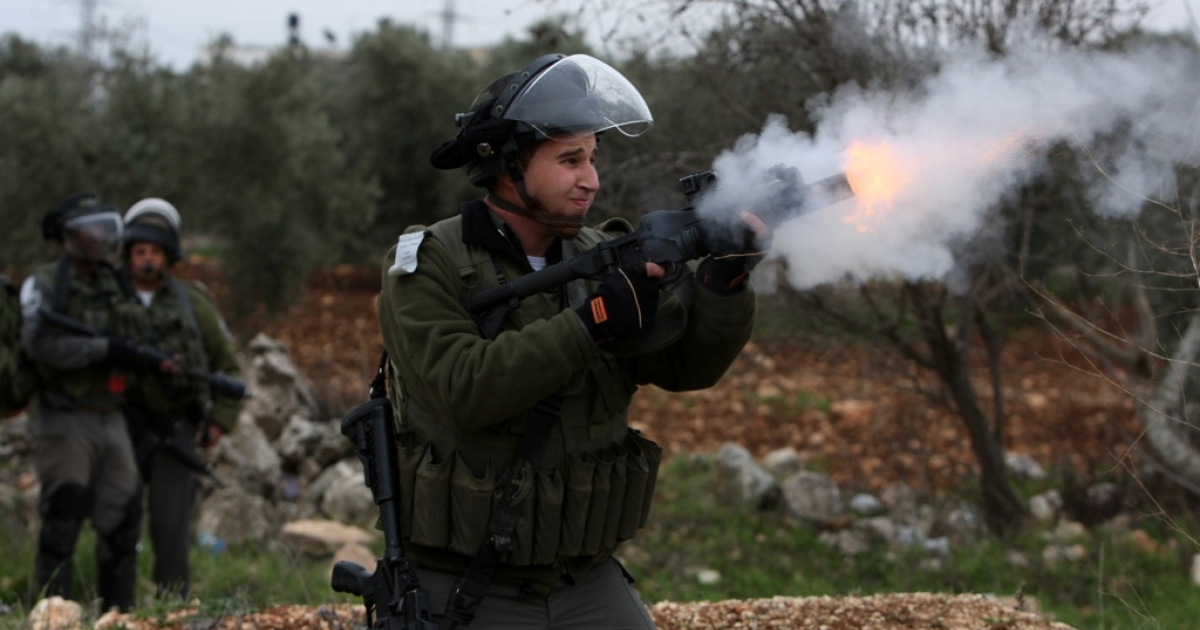 An Israeli soldier fires his weapon at Palestinian youths during clashes following a protest against Israel's controversial separation barrier in Qalandia, near the West Bank city of Ramallah, on Dec. 30, 2011.</p>