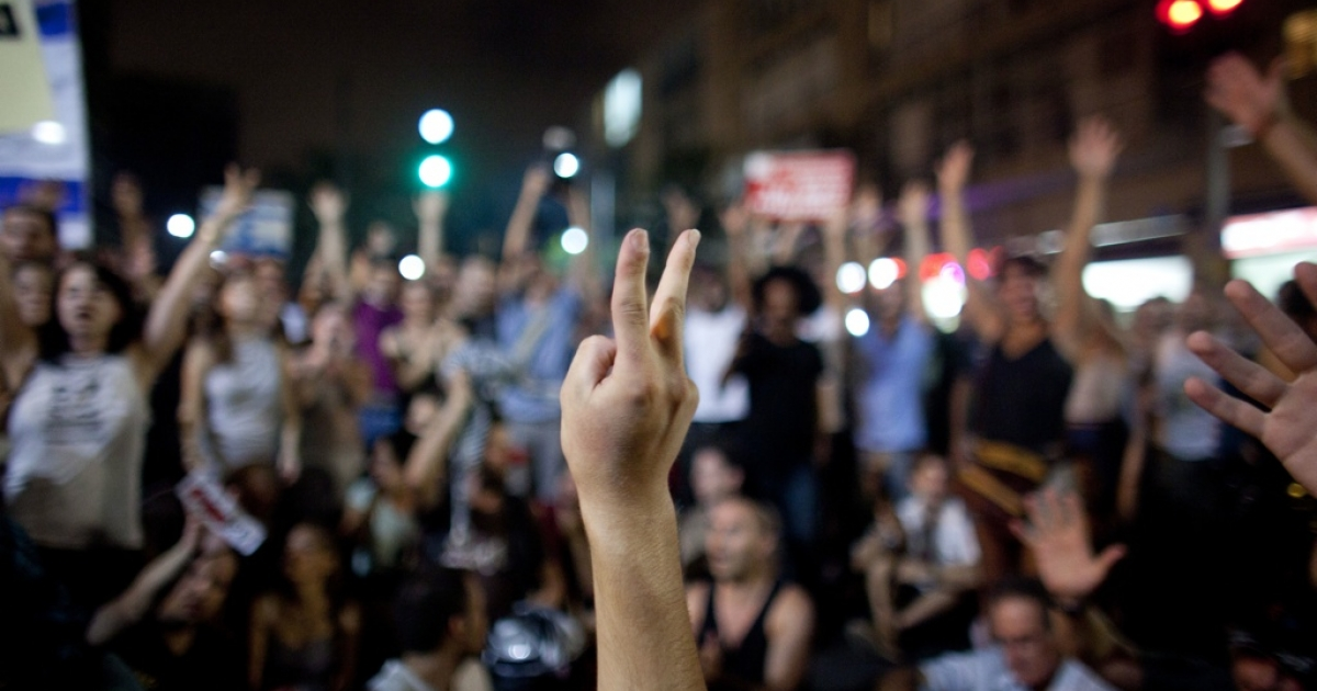 An Israeli youth flashes a V-sign as Israelis protest against rising housing prices and social inequalities on July 30, 2011 in Tel Aviv, Israel.</p>