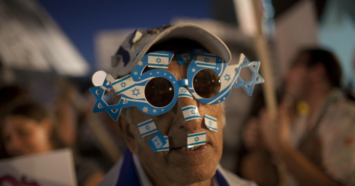 One of an estimated 400,000 Israelis demonstrates in the center of Tel Aviv on Sept. 3, 2011 protesting against rising housing prices and social inequalities in the Jewish state.</p>