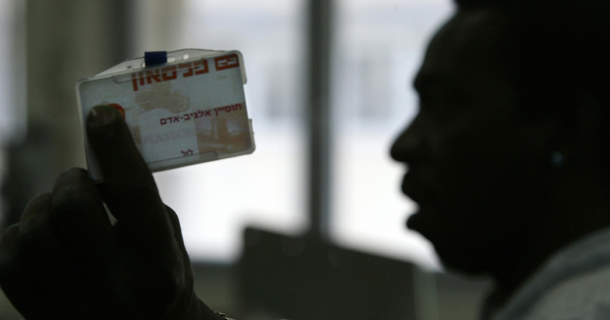 A man shows his Israeli ID card.</p>