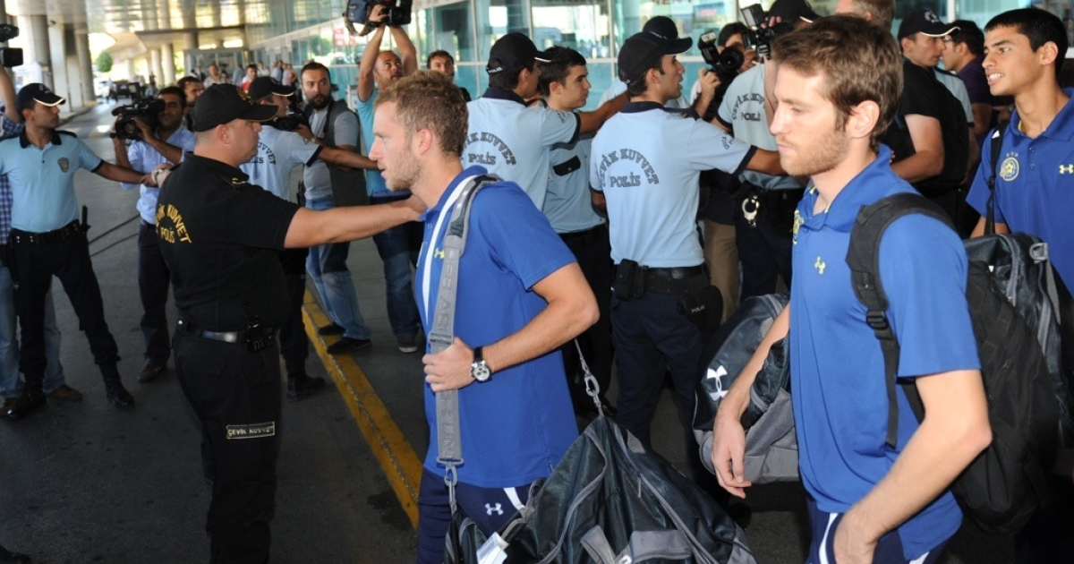 Turkish riot police stand guard as Maccabi Tel-Aviv players walk towards a bus at Ataturk Airport in Istanbul, on Sept. 14, 2011.</p>