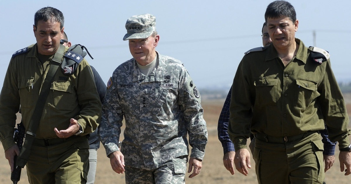 US military chief Martin Dempsey (C) walks with Israeli military personnel during a visit to the Iron Dome command center in Israel on Oct. 30, 2012.</p>