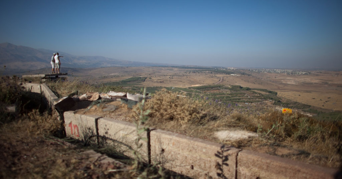 Israelis look at the nearby Syrian village of Jebata al-Khashabn from an Israeli army post near the village of Buqaata at the Israeli side of the border on July 24, 2012 in the Golan Heights.</p>