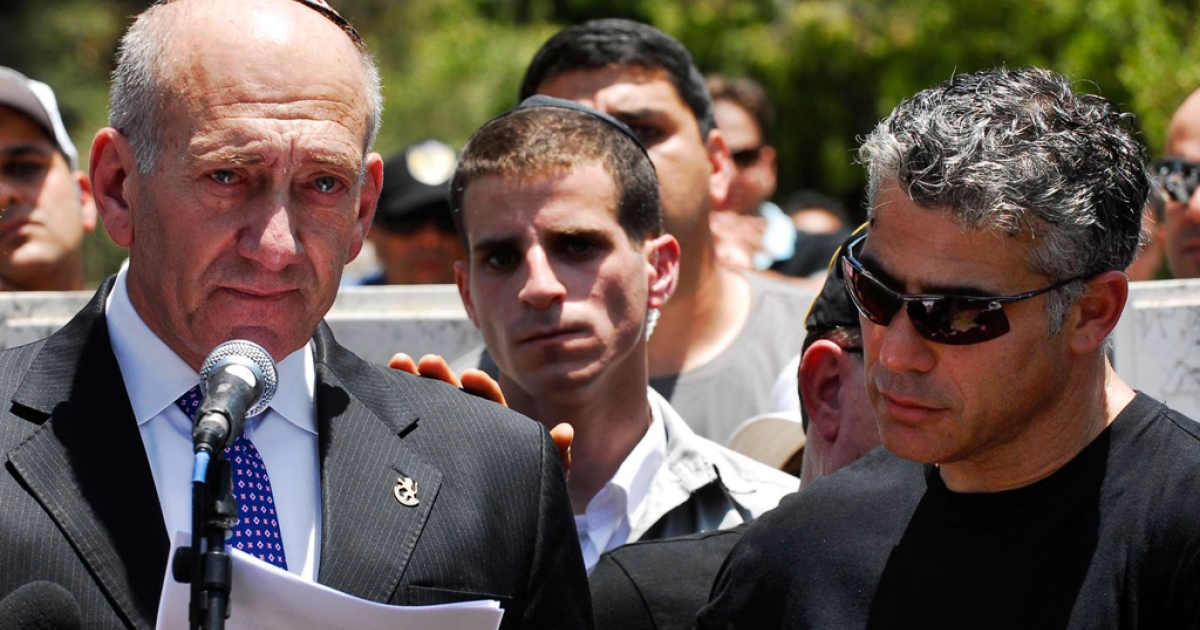 Former Israeli Prime Minister Ehud Olmert is comforted by Yair Lapid as he speaks during the funeral of Lapid's father, Yosef (Tommy) Lapid, a former cabinet member and journalist who succumbed to cancer at the age of 77 the day before, on June 2, 2008 in Tel Aviv.</p>