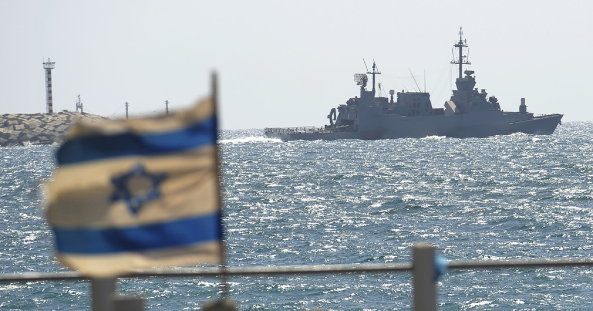An Israeli flag flutters as a military vessel leaves the navy port of Ashdod in southern Israel on June 5, 2010</p>