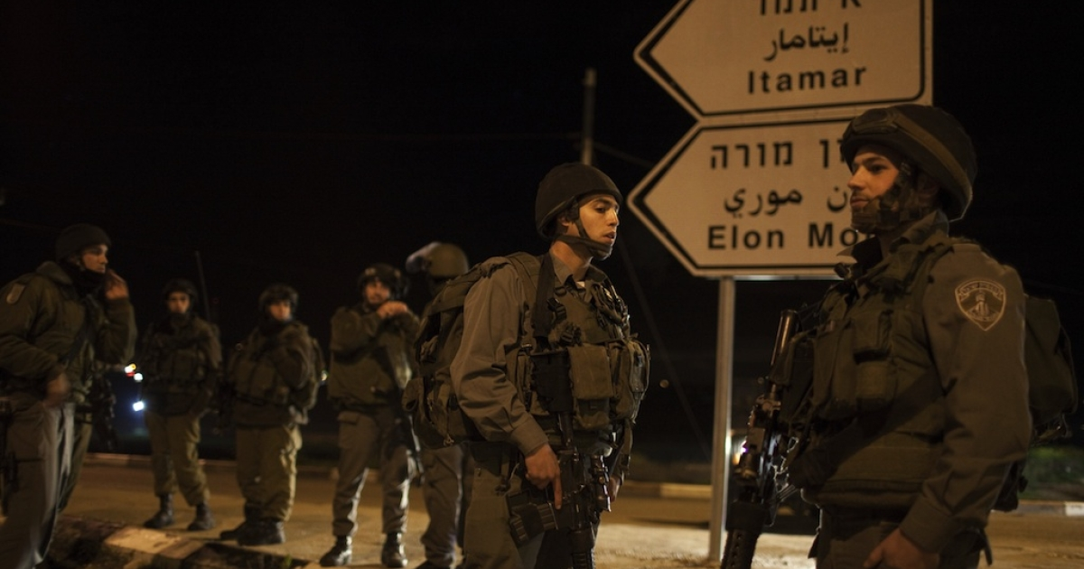 Israeli soldiers block the road at the Hawara checkpoint south of the West Bank city of Nablus on March 12, 2011, after a Palestinian killed five Israelis in an overnight attack in the Jewish settlement of Itamar.</p>
