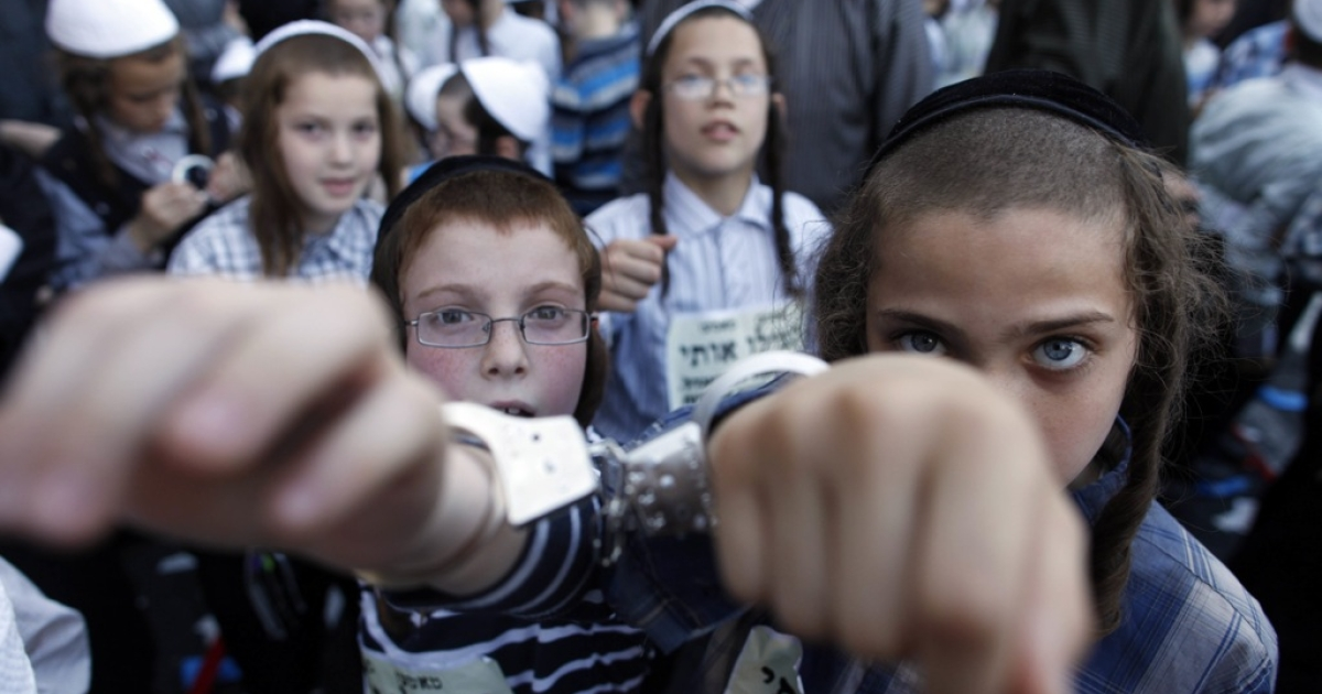 Ultra-Orthodox Jewish children wear handcuffs as they protest against a uniform draft law to replace the Tal Law in Jerusalem, Israel on July 16, 2012. The Tal Law, which exempts ultra-Orthodox yeshiva students from mandatory military service, was declared unconstitutional by the High Court in February, and is due to expire in August.</p>