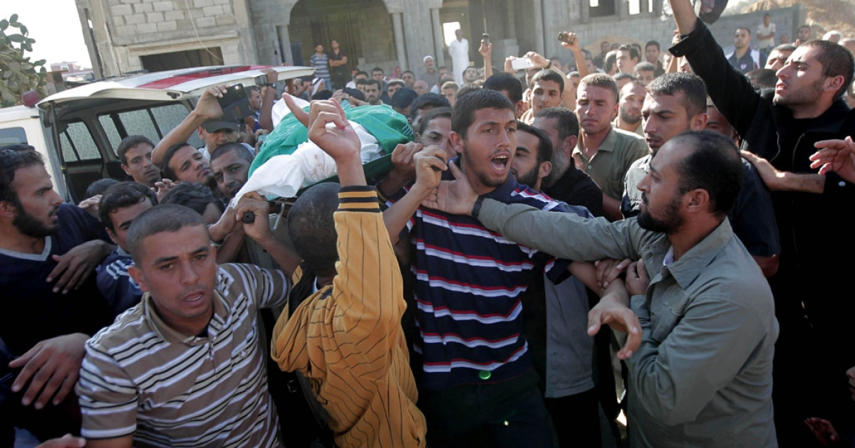 Palestinians carry Suleiman Kamel al-Qara's body during his funeral procession in Khan Yunis, Gaza, on October 28, 2012, after he was killed in an Israeli airstrike earlier in the morning.</p>