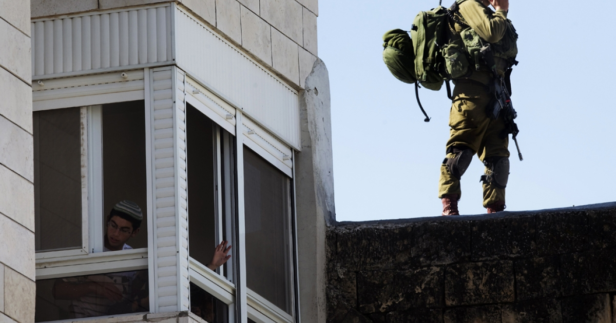 An Israeli settler looks out the window of an occupied Palestinian house as an Israeli soldier stands guard in the center of Hebron in the occupied West Bank. The Jewish settlers who took over the Palestinian property were evicted on April 4, 2012 by Israeli security forces.</p>