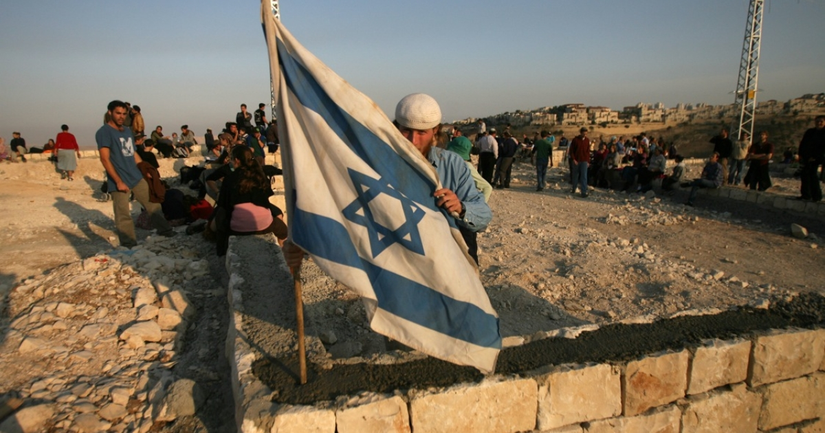 A Jewish settler raises an Israeli flag at the E1 settlement area on December 9, 2007, near the Israeli settlement of Maale Adumim in the West Bank.</p>