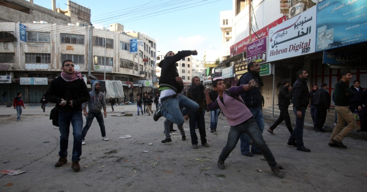 Palestinian youths throw stone at Israeli forces during clashes in the West Bank city of Hebron on December 06,2012.</p>