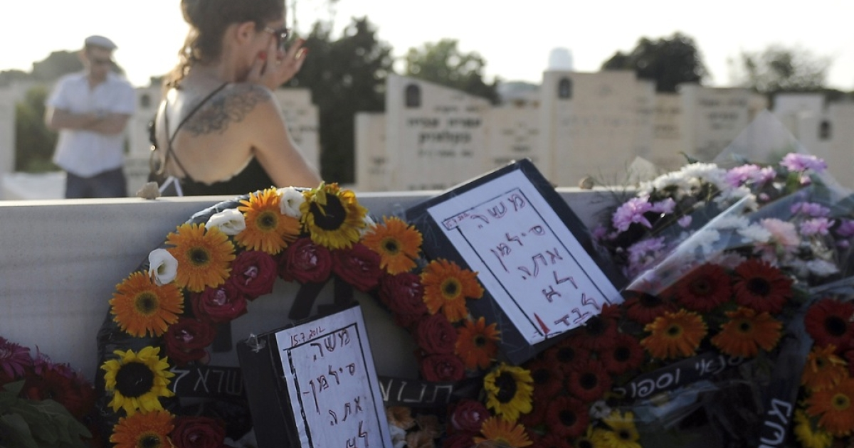 An Israeli woman walks past the grave of Moshe Silman during his funeral in the city of Holon on July 22, 2012, following his death from severe burns after he set himself alight during a social justice demonstration on July 14.</p>